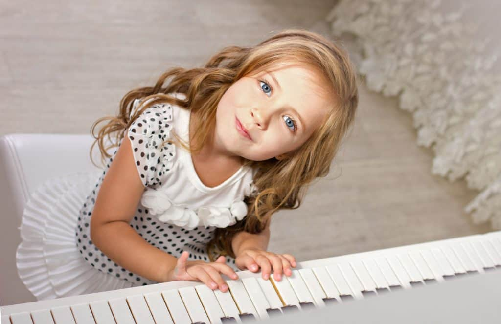 Beautiful little girl sits next to a piano