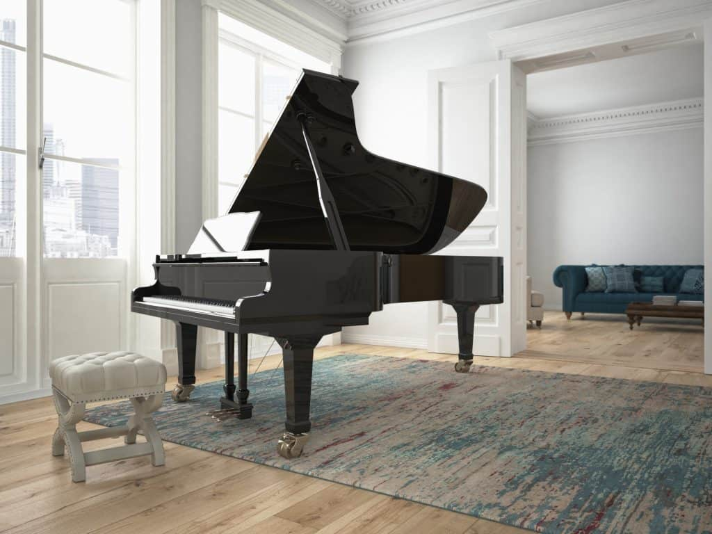 Black piano with a white bench in a living room