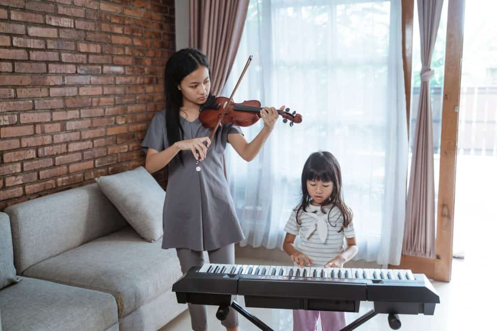 Little asian girl plays piano with her sister playing violin together