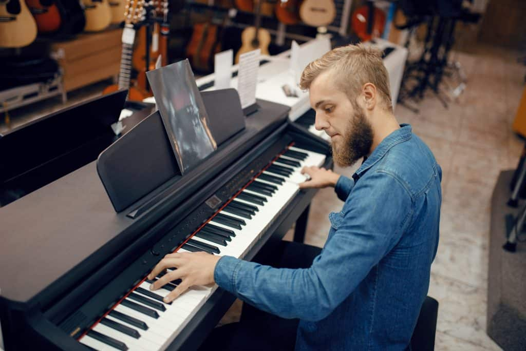 Man plays digital piano in a music store