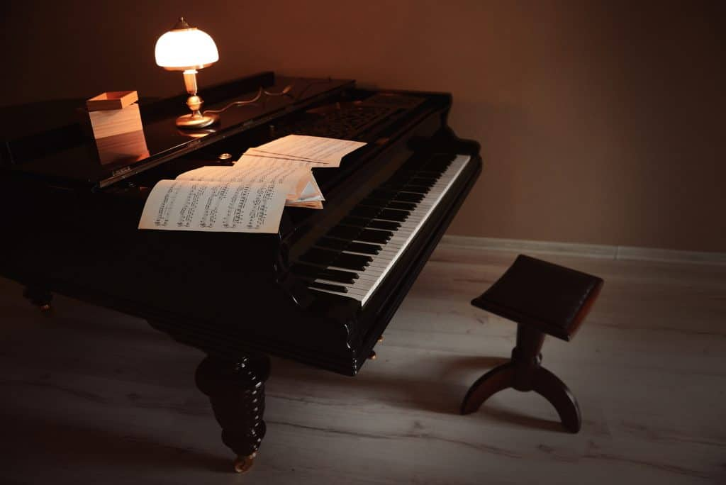 Piano lamp on top of an old classical piano