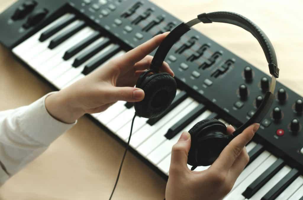 Woman holding headphones over her digital piano